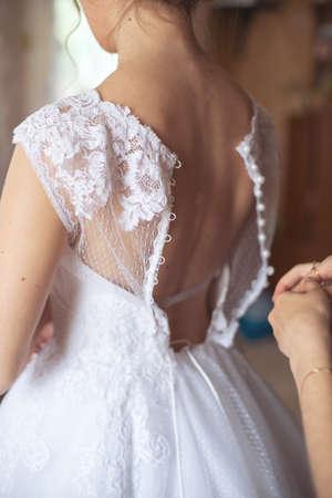 The bride wears a dress,
