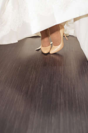 Brides feet in shoes playfully peek out from under the hem of a wedding dress