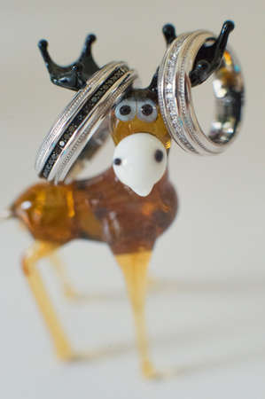 Wedding rings hanging on the horns of a toy deer, close-up Standard-Bild - 129351569