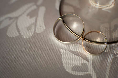 Gold wedding rings lie on the table close-up Standard-Bild - 129351594