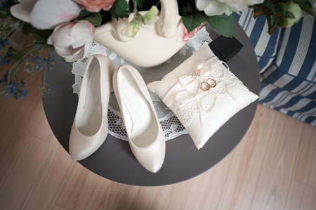 Shoes, wedding ring pads, rings on the table