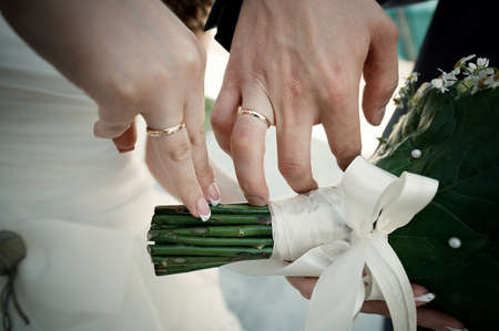 The bride and grooms hands with rings