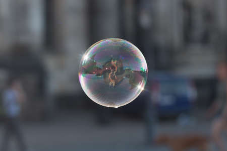 Soap Bubble Floating in the air and sparkling, illuminated by the last rays of the sun in the city of alicante in spain