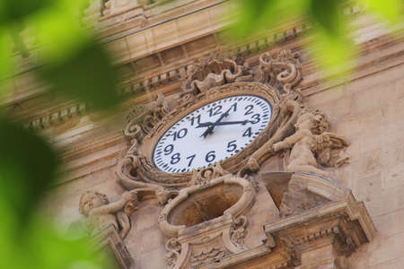 Old Sophisticated Clock On The Wall Of an old building in alicante in spain Stock Photo