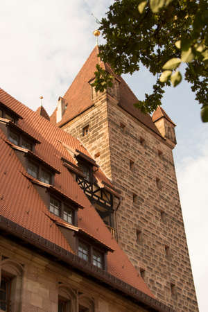 Nuremberg Castle With a Red Pile roofs and an old tower framed by the leaves of a tree, shot in the forenoon of a sunny summer day Editorial