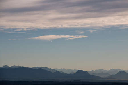 Blue sky with clouds and a few summits of the mountain chain of the alps in bavaria