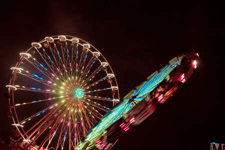 Two ferris wheels spinning next to each other with colorful lightpainting on a bavarian fair in germany at night, shot with long exposure Stock Photo