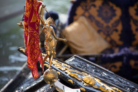 Close up of a golden gondola statue with gold and blue ornaments in the venice canal in italy