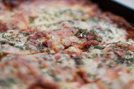Close up shot of a italian lasagna topping with cheese, tomato sauce, rocket and other herbals Stock Photo