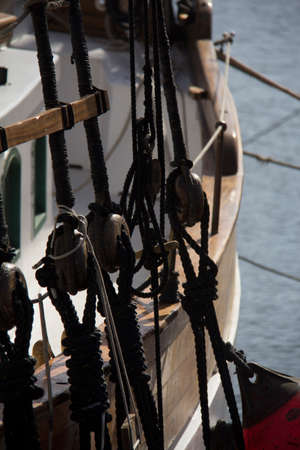 The black ropes of an old sailing boat with wooden boards and the sea in the background in cartagena in spain Stock Photo