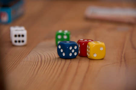 Game Dices In The Colors Red, Green, Blue, White On A Wooden Table With Game Equipment In The Background