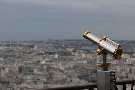 golden and silver vintage binoculars on a platform of eiffel tower with paris in background Stock Photo