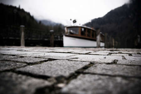 old ferry boat at the lake in bavaria with the famous lake in the background and cobblestone in the unfocused front
