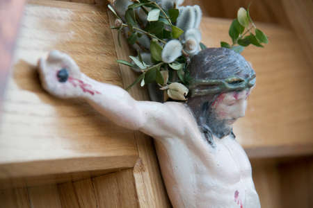 Jesus Christ figure on a wooden wayside cross with catkins behind his neck as part of a wayside cross at bavaria in germany