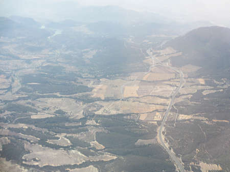 Aerial of the area around the Alicante airport with hills and fields shot out of a plane