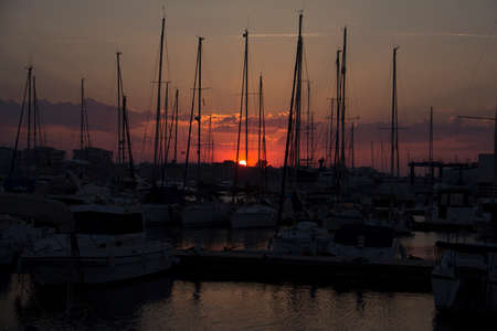 Sailing boats and other silhouettes of the masts with a sunset in the background in torrevieja in spain