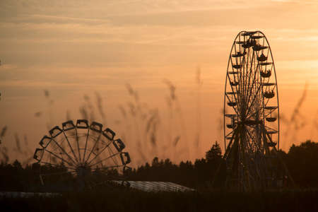 Two rotating ferris wheels in the evening sun with a cloudy orange sky and grass blades on the unfocused foreground, shot aa bavarian folk Stock Photo