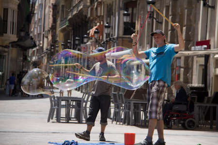MURCIA, SPAIN JUNE 09 2014: Two soap bubble artists with two big soap bubbles on their sticks with reflections in the bubbles