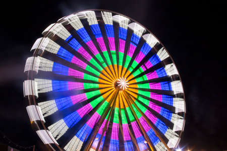 ferris wheels spinning with colorful lightpainting on a bavarian fair in germany at night, shot with long exposure