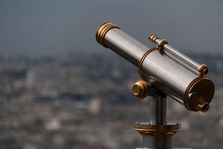 golden and silver vintage binoculars on a platform of eiffel tower