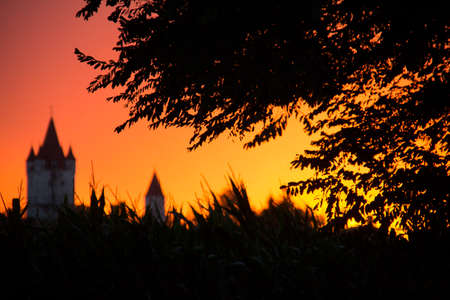 Old mediaval tower the castle at Haag in upper bavaria in the glowing orange and yellow sunset light and the silhouette of trees and grass in the foreground Stock Photo