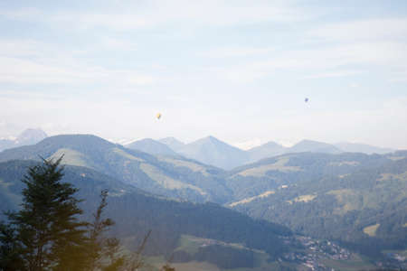 Mountain view panoramic in the Alps with two balloons flying
