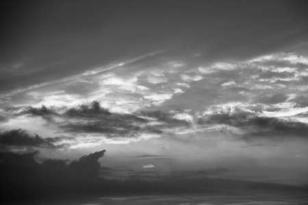Glowing morning sky with the sun illuminating the sky and clouds in black and white dramatic cloudscape Stock Photo