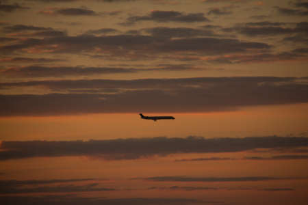 Silhouette of a flying plane in the clouds of an evening sky after sun set with orange sky Stock Photo
