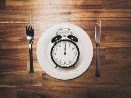 Plate with black vintage Alarm Clock showing Twelve O'clock as symbol for intermittent fasting Stock Photo