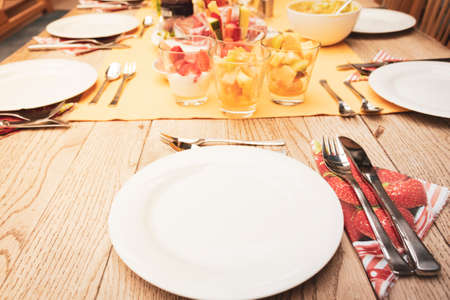 set famiily breakfast table with small glass bowls full of fruits and fish, yellow tablecloth, silver cutlery, white plates on wooden table