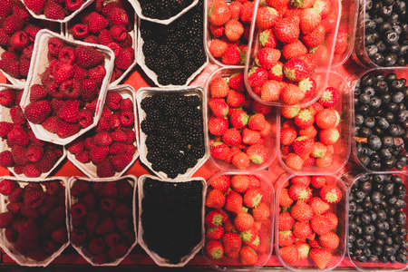 bowls or shells of juicy raspberries, blackberries, strawberries and blueberries on a local street market in stockholm Stock Photo