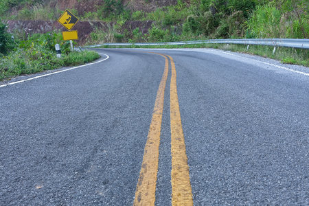 Asphalt road,straight ahead with a warning sign to watch the fallen stone.