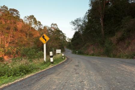 Panneau d'avertissement. Sur la route devant vous se trouve la double courbe, la première à gauche dans la campagne thaïlandaise. Banque d'images