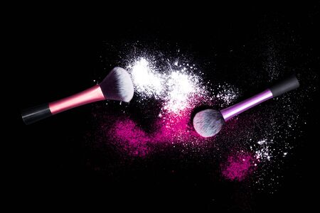 pink powder: Make-up brushes with colorful powder on black background. Explosion stars dust with bright colors. White and pink powder. Stock Photo