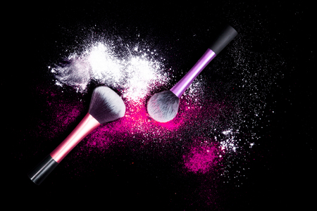 black makeup: Make-up brushes with colorful powder spilled glitter dust on black background. Makeup brush on party with bright colors. White and pink powder.
