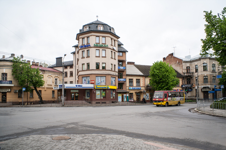 obelisk stone: IWANO- FRANKIWSK, UKRAINE - MAY 1, 2017 ; Townhouses and shops at the crossroads.