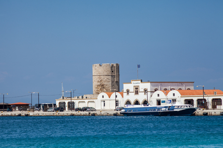 Harbor and monuments in Rhodes. Old defensive stands and windmills. Wharf harbors, boats and sailing ships. Historic harbor, pier and beach.