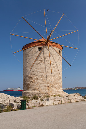 Windmill Papagiorg whit Vati in Rhodes harbor. Old defensive stands and windmills. Wharf harbors, boats and sailing ships. Historic pier and beach.