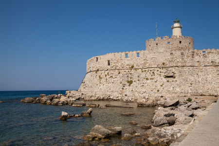 Santa Claus Fortress on the pier in Mandraki Harbor. Bastion of defense on the quay of Rhodes. A defensive building in a harbor in the town of Rhodes with a lighthouse.
