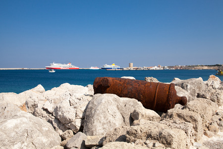 Old rusty cannon next to the Santa Claus Fortress in Rhodes. In the background sea and passenger ships. Editorial