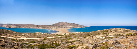 windsurf: Beach between two seas. Beach between the islands of Rhodes and Prasonisi. Road across the sea. People practicing Kitesurfing. Colorful kites on the sea shore. Blue waves sea and sky.