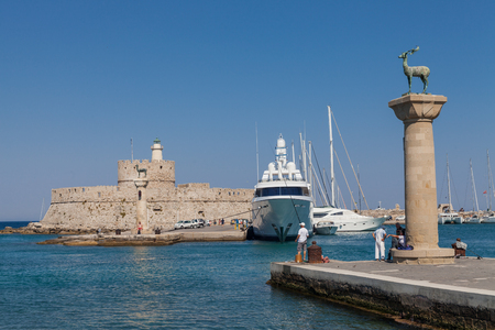 photo edges: Statue Deer and hound and columns in Mandraki harbor. On background Santa Claus Fortress. Place where was statue, colossus from Rhodes. Symbolic gate to the harbor.