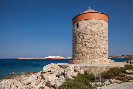 photo edges: Windmill Papagiorg whit Vati in Rhodes harbor. Old defensive stands and windmills. Wharf harbors, boats and sailing ships. Historic pier and beach.