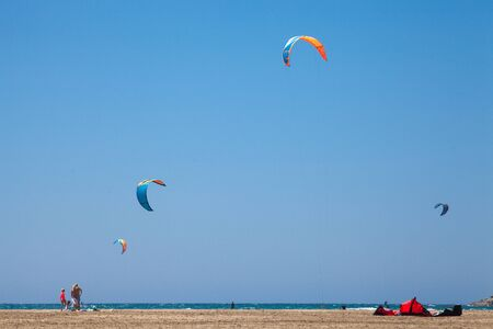 People practicing Kitesurfing. Beach on the peninsula Prasonisi, Rhodes. Colorful kites on the sea shore. Blue sea and windsurfing.