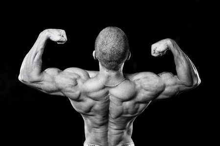 Back muscles. The athlete flexes his muscles. Bodybuilder presenting his body. Stock Photo