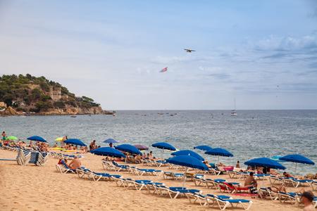 Beach off the coast of Lloret de Mar, Costa Brava. People on the beach in spain lie on sun loungers under umbrellas. Resting under a castle on the beach in Lloret de Mar. Castell de Sant Joan