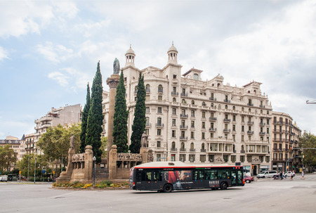 Crossing the streets of Barcelona. Statue of De Sant Joan. Public transport bus on one of the main roads.