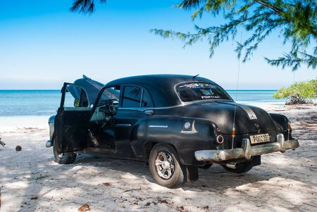 Old black Pontiac in the Gulf of Mexico.The beach of Cayo Jutias in Cuba old car and blue sea. Holiday in tropic. 版權商用圖片 - 128139760