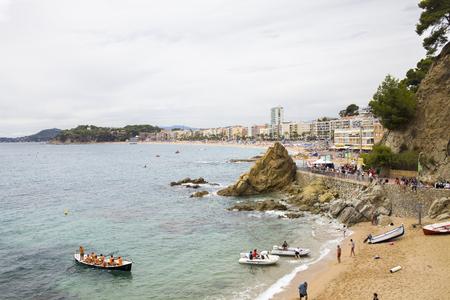 Lloret de Mar  Spain - June 27, 2018: Beach off the coast of Lloret de Mar, Costa Brava. People on the beach lie on sun loungers under umbrellas. Resting under a castle on the beach in the city.