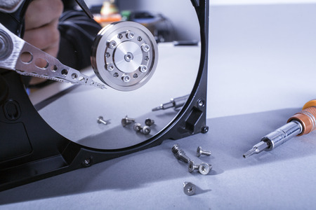 Hard disk drive platter. Open hdd hard disk. Data recovery from damaged media. Disk head above the plates